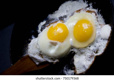 two fried eggs. on a wooden spatula. Against a dark background.