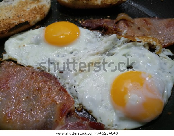 two fried eggs with two slices of back pork bacon in a non-stick pan