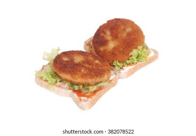 Two fried hamburger beef patties with lettuce, tomato sauce and mayonnaise on toast. Image isolated on white studio background.