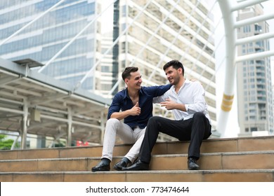 Two friend sitting down on stairs shaking hands. Businessmen very happy after success project. concept of business marketing, negotiation, compliment and management.