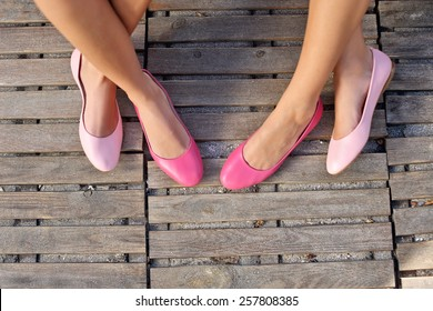 two friend women sitting cross legged wearing pink flats