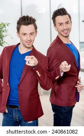 Two friendly brothers twins in red jackets and blue sweater together having fun in the dinner room or the restaurant. Family relationships or friends in business