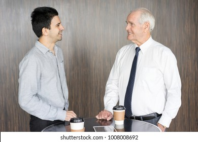 Two Friendly Businessmen Discussing Deal at Cafe