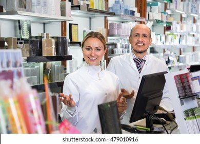 Two friendly diligent female and male pharmacists in white coats working the pharmaceutical store