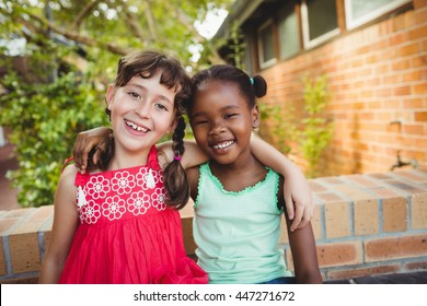 Two friendly girl posing and smiling at the camera