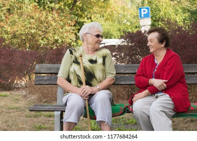 Two friendly grannies talking on a bench