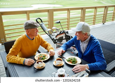 Two friendly senior men sitting in outdoor cafe, having lunch and discussing curious moments of the last game of golf