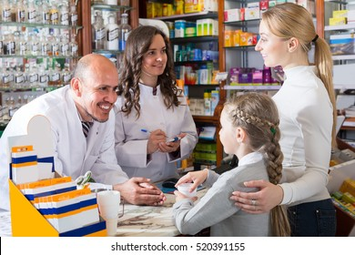 Two friendly smiling pharmacists wearing white coats standing next to cashier and consulting a customer with child.
