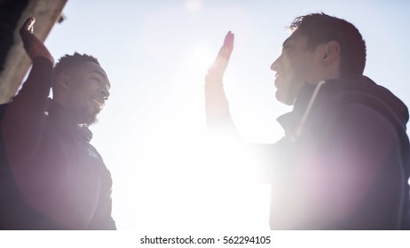 Two friends about to high five in the sunlight, teamwork concept