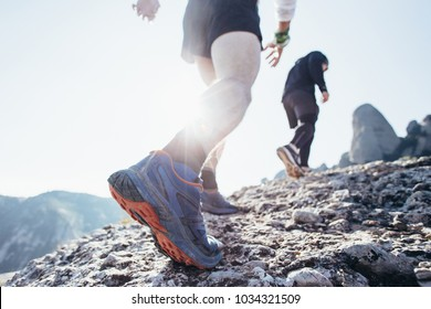 Two friends or athletes run on rocky mountain terrain on path or trail high in mountains or on coast, healthy lifestyle choice and hard workout plan. Sun flare into lens, inspiring movement