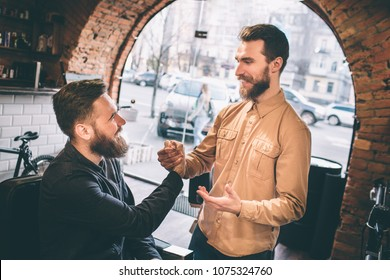 Two friends are in a barbershop. They are shaking each other's hands. Guys are smiling to each other.