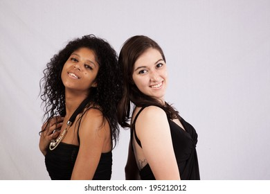 6eb79d078e5 Two friends, a black woman and a Hispanic woman, both wearing black dresses  and