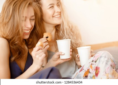 Two friends of the blonde have fun laughing, drinking coffee and eating croissants. Concept Breakfast in bed, friendship, sisterhood