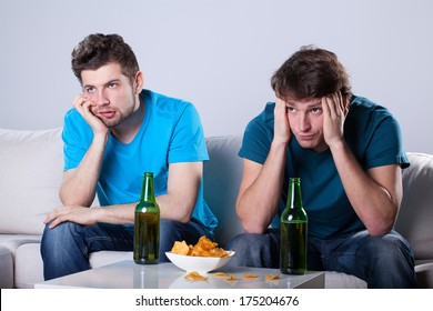 Two friends bored over bottles of beer and nachos