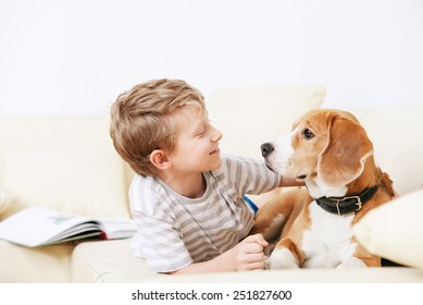 Two friends - boy and dog lying together on sofa
