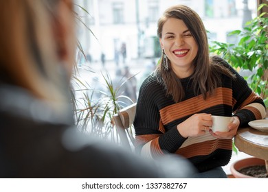 two friends in a cafe by the window