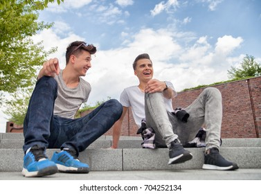 Two friends casual wear sitting on stairs in town and laughing, best friend concept