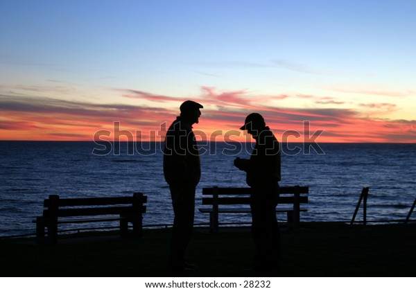 two friends chat in the setting sun in laguna beach california the evening before a major rain storm rolled in
