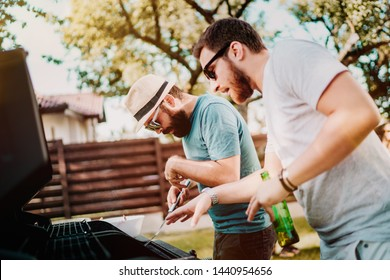 Two friends cooking and having fun on a barbecue grill during sunday backyard party