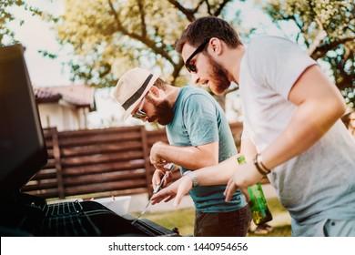 Zwei Freunde kochen und beim Grillabend auf dem Hinterhof Spaß haben