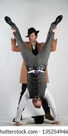 two friends dressed in vintage clothes in classic style and stand upside down and fool around on a white background
