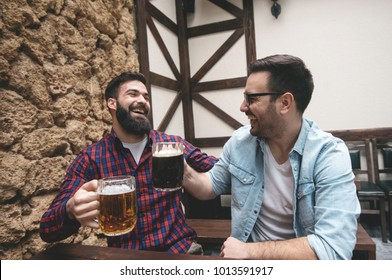 Two friends drink beer in the pub.