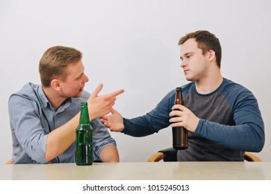 Two friends drinking beer at home and talking about something.