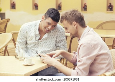 Two friends drinking coffee and talking in the cafe bar