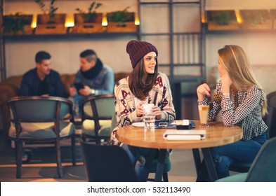 Two friends enjoying coffee together in a coffee shop as they sit at a table chatting