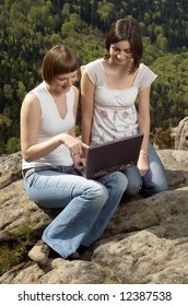 Two friends enjoying free time with laptop
