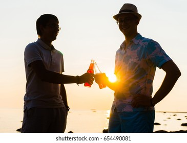 Two friends enjoying a sunset on a beach and drinking a beer. Young, freedom, beach, summer, concept.