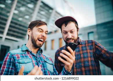 Two friends enjoyng victory after betting  in mobile gambling application. Men using mobile phone to know winning results. Football stadium on the background.