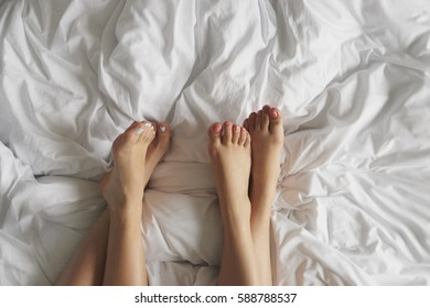 two friends feet hanging out at home in bed morning after pajama party