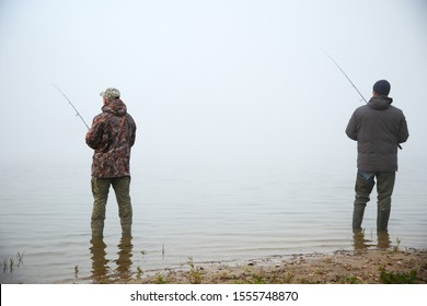two friends fishermen fishing on the river in fog