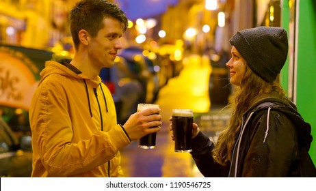 Two friends in front of an Irish pub drinking beer