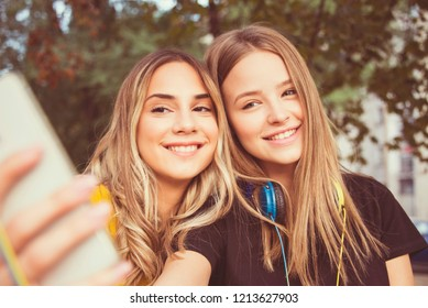 two friends girls with smartphone beautiful close up outdoor making selfie, teen trendy hairstyle and make up autumn colors sunshine day