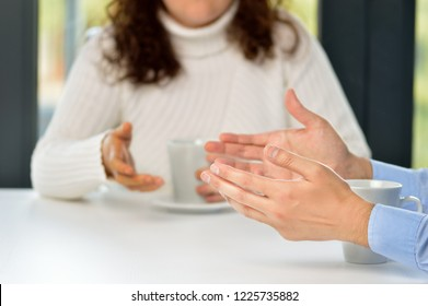 Two friends hands talking in a bar