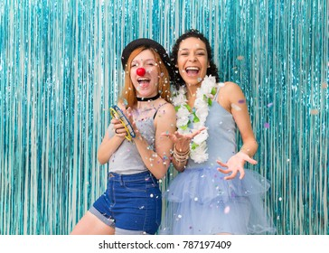 Two friends have fun at Carnaval. One is wearing clown nose and the other Hawaiian necklace. Predominance of color Blue. Women play confetti and giggle. Funny girl plays tambourine.
