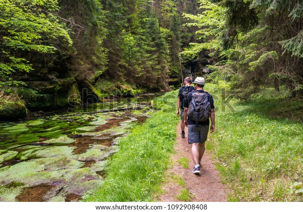 Two friends hiking along a river in the mountains