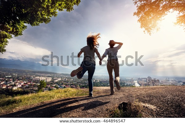 Two friends holding hands and running to the beautiful view of city panorama in the mountains at rainy dramatic sunset