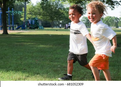 Two friends are holding hands as they run through a park. One little boy is black and the other is white. Celebrate diversity, race concept