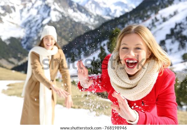 Deux amis plaisantant en lançant des boules de neige en vacances dans une montagne enneigée en hiver
