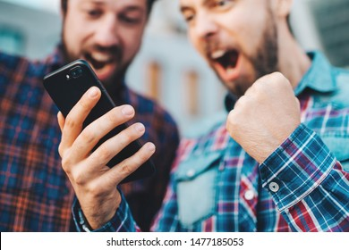 Two friends looking extremely excited getting good news  winning a bet in online bookmaker watching broadcast with winner results on mobile phone. Football stadium on the background. Focus is on hand.