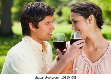 Two friends looking eye to eye and linking their arms while holding glasses of red wine in a park