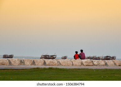 two friends looking at fishing boats at the corniche