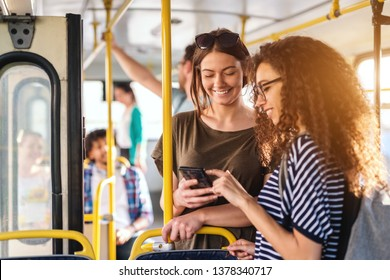 Two friends looking in phone while standing on a bus.
