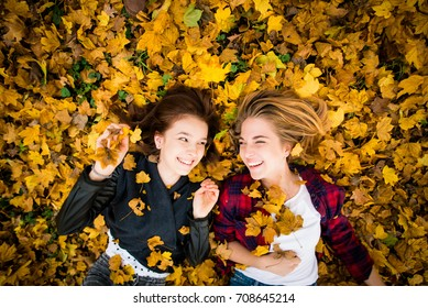 Two friends lying on ground in fallen leaves and having fun - above view