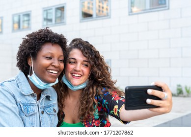 two friends make a selfie in time of epidemic with masks down, couple of multi-ethnic friends pose for social media