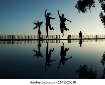 two friends making fun as silhouette at a sunset beach in morocco