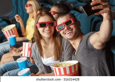 Two friends making selfie in the cinema